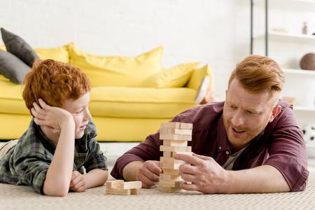 gelukkig roodharige vader en zoon spelen met houten blokken thuis
