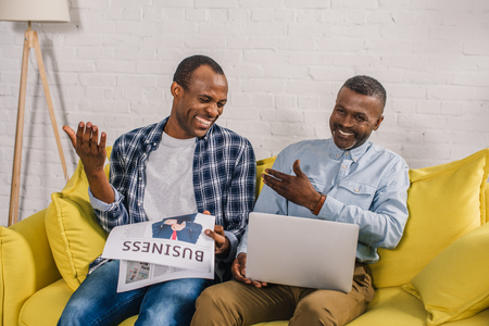 happy senior man and adult son reading business newspaper and using laptop on sofa at home Stock Photo