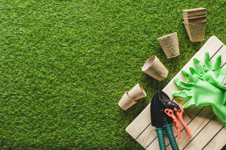top view of flower pots, protective gloves and gardening tools on grass