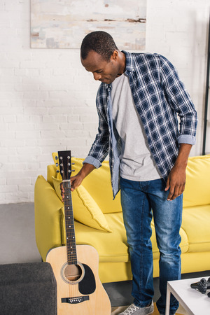 young african american man holding acoustic guitar at home