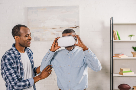smiling young man looking at senior father using virtual reality headset at home Stock Photo