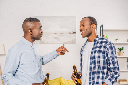 happy father with smiling adult son drinking beer and talking at home