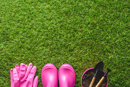 top view of rubber boots, protective gloves, flower pot with gardening tools on lawn Banco de Imagens