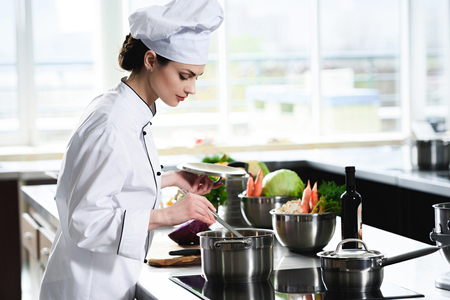 Chef mujer cocinando en sartén en la estufa de la cocina