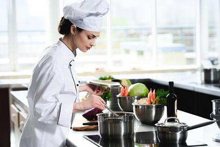 Vrouw chef-kok koken in de pan op fornuis