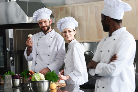 Multiracial team of cooks choosing cooking ingredients on modern kitchen Stock Photo