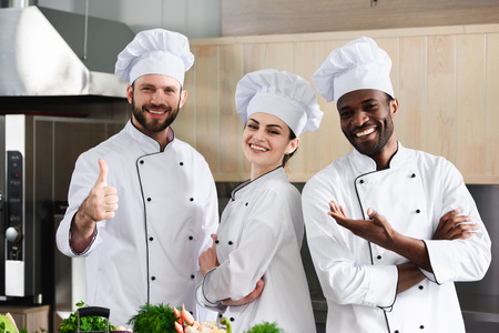 Male cook showing thumb up by his multiracial team