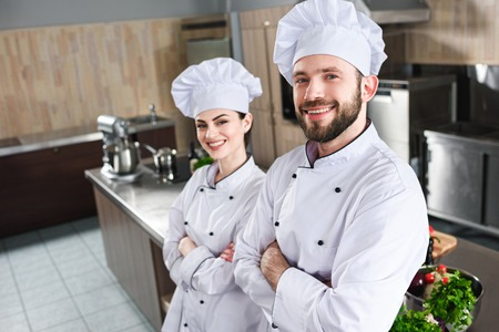 Professional team of male and female cooks standing with folded arms on kitchen Stock Photo