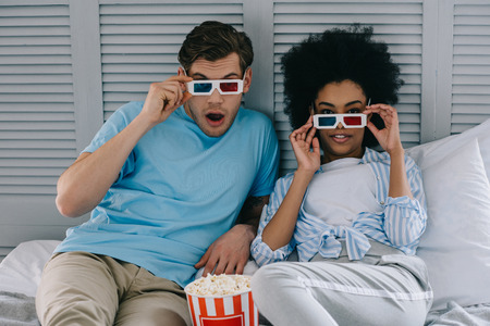 Multiracial boyfriend and girlfriend in stereoscopic glasses watching movie at home with popcorn Archivio Fotografico