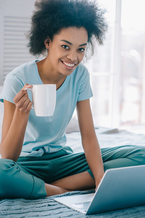 Smiling african american girl in lounge wear holding cup of coffee and using laptop in bed Stock Photo