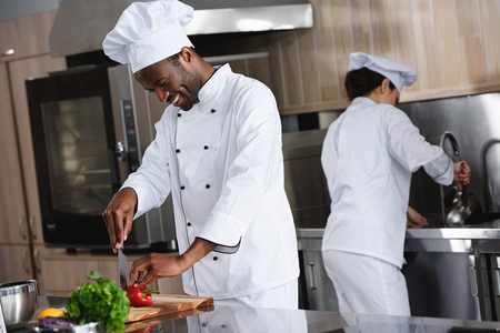 african american chef cutting bell pepper at restaurant kitchen