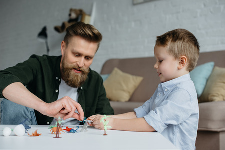 father and cute little son playing with various toy dinosaurs together at home Imagens