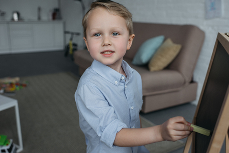 side view of little boy with piece of chalk looking at camera while drawing picture on blackboard at home