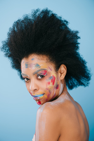 attractive young woman with paint strokes on face isolated on blue Stock Photo