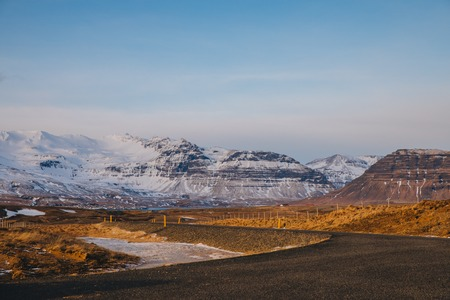 beautiful icelandic landscape with empty road and snow-covered mountains