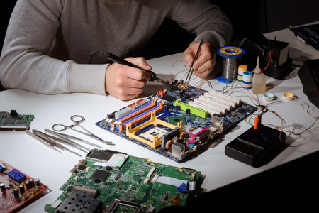 Engineer working with soldering equipment and motherboard