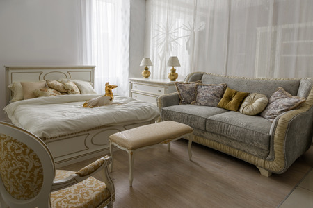 Dog statuette on bed with white linen in elegant room