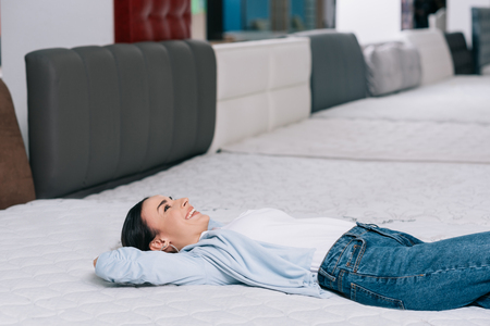 side view of smiling customer lying on orthopedic mattress in furniture store