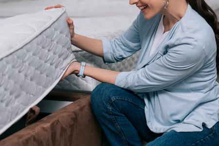 Photo recadrée de femme souriante en choisissant un matelas orthopédique dans un magasin de meubles