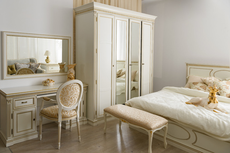 Elegant dressing table by bed in stylish room Stock Photo