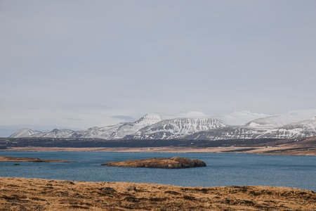 beautiful landscape with rocky mountains covered with snow and cold water of gulf in iceland, hvalfjardarvegur 写真素材