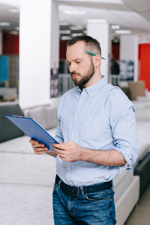 portrait of focused shop assistant with notepad in furniture shop with arranged mattresses Banco de Imagens