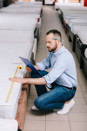 shop assistant with notepad and measuring mattress with measure tape in furniture shop 版權商用圖片