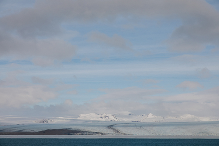 beautiful scenic landscape with snow-covered hills, water and cloudy sky, iceland, Jokulsarlon Glacier 写真素材