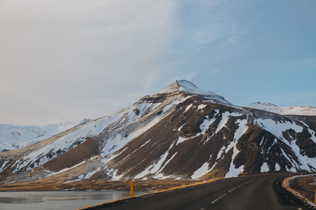 empty asphalt road and snow-covered mountains in iceland