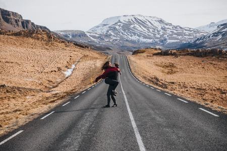 happy young couple hugging on road in iceland, hvalfjardarvegur 写真素材