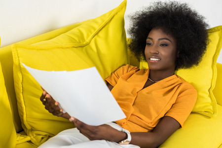 smiling african american woman with papers remote working on sofa at home
