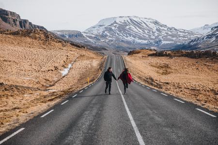 young couple holding hands and walking on asphalt road in iceland, hvalfjardarvegur