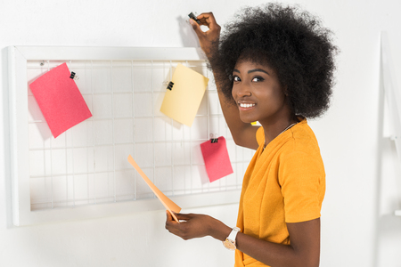 smiling african american freelancer putting empty colorful papers on board at home office