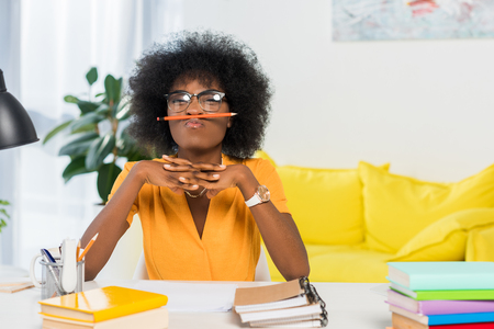 portrait of african american freelancer in eyeglasses with pencil at workplace at home office Stockfoto
