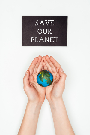 cropped image of woman holding earth model in hands under sign save our planet isolated on white, earth day concept Stock Photo