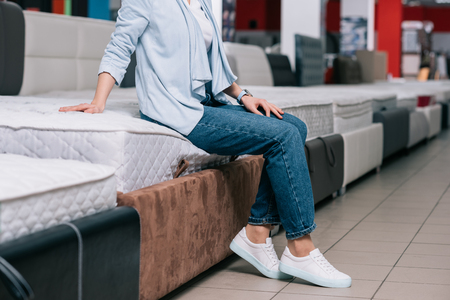 partial view of woman sitting on mattress in furniture shop Stockfoto
