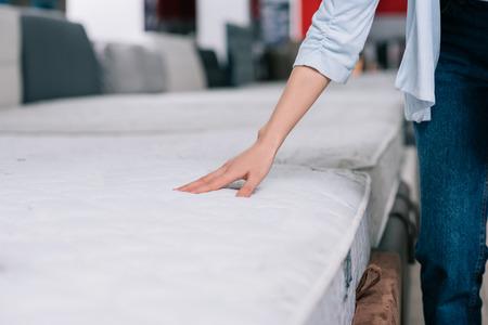 Vista parcial de la mujer tocando el colchón ortopédico en la tienda de muebles Foto de archivo
