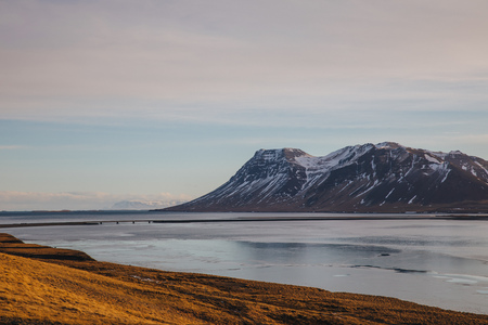 beautiful scenic view of snow-covered mountains and gulf with bridge in iceland 写真素材