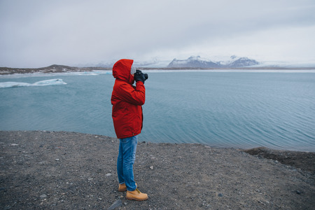 side view of person holding camera and photographing spectacular icelandic landscape, Jokulsarlon Glacier 写真素材