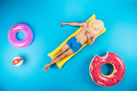 top view of young man in shorts resting on inflatable mattress on blue, summer vacation concept