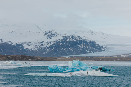 beautiful landscape with snow-covered rocky mountains and icebergs in water, iceland, Jokulsarlon Glacier 写真素材