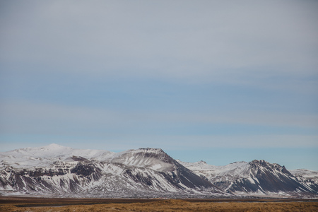 beautiful snow-covered mountains and plain with dry grass in iceland, snaefellsnes