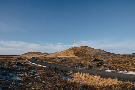 empty road and lighthouse on hill at sunny day in iceland, valahnukamol, reykjanes