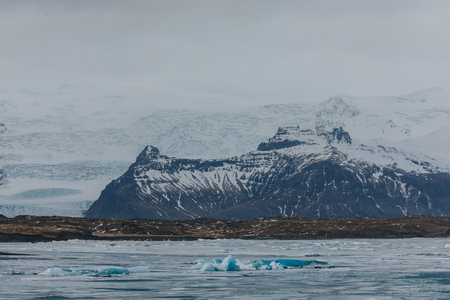 majestic icelandic landscape with snow-covered rocky mountains and icebergs in water, Jokulsarlon Glacier