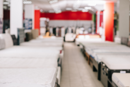 interior of furniture store with arranged mattresses around