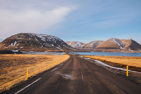 empty asphalt road, snow-covered mountains and gulf in iceland