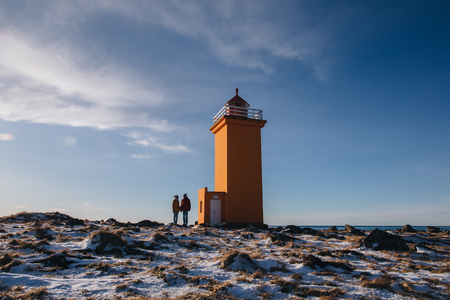 young couple holding hands and standing near lighthouse in iceland, stafnesviti, reykjanes 写真素材