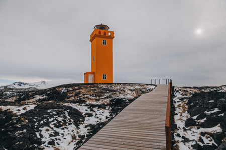 lighthouse and wooden walkway at cloudy day in iceland, svortuloft 写真素材