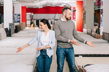 couple pointing at mattresses around in furniture store