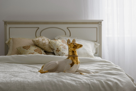 Dog statuette on bed with white linen in room